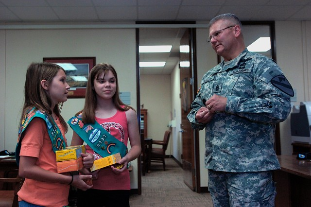 FORT HOOD, Texas - Madison Gray (left) and Gillian Herman, Girl Scouts with Girl Scout Troop 8737, from Frisco, Texas, receive a challenge coin from Command Sgt. Maj. Rory Malloy, 1st Cav. Div., for donating 116 boxes of Girl Scout cookies to the division's Soldiers.