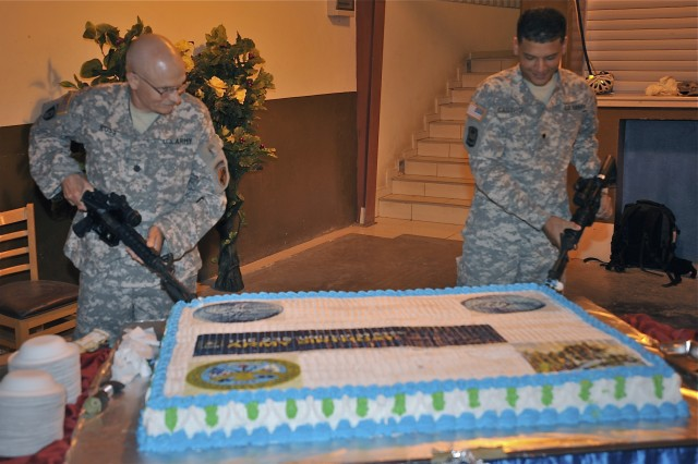 CAMP LEMONNIER, Djibouti (Jun. 5, 2010) U.S. Army Lt. Col. Ronald Ross (left) and Spc. Victor Castro participate in the long-standing tradition of the youngest and oldest to cut the cake at the Army's 235th Birthday celebration June 5. Ross is a member of the Army's 353rd Civil Affairs Battalion and Castro is a member of the Army's 1-65th Battalion, Delta Company, both attached to Combined Joint Task Force-Horn of Africa. CJTF-HOA includes more than 700 U.S. Army active, reserve and National Guard members. (U.S. Navy photo by MC1 Larry Foos/Released).
