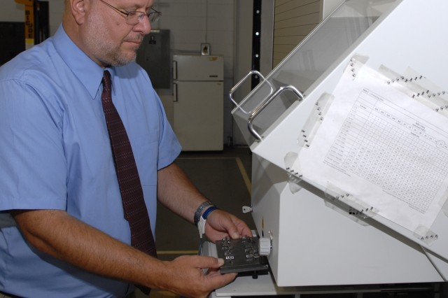 """Michael Oravitz places a tray of integrated circuits into an X-ray Fluorescence Spectrometer to determine the lead content of the solder.  If the content is less than the required 3 percent, the spectrometer will alert him.  Solder that has less than 3 percent lead can develop """"tin whiskers"""" that can damage a circuit, rendering electronics systems unreliable.  Oravitz is an electronics technician at Tobyhanna Army Depot."""