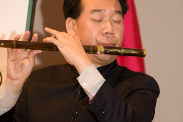 "Da Chen, an author of books about his native China, plays ""Danny Boy"" on a bamboo flute for Anniston Army Depot's Asian Pacific Islander Heritage luncheon crowd."