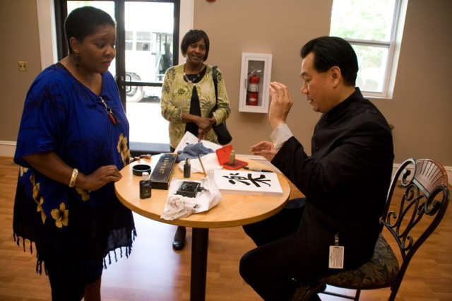 Da Chen, speaker for Anniston Army Depot's Asian Pacific Islander Heritage luncheon, signs an autograph for Shenita Miller of the Directorate of Resource Management.