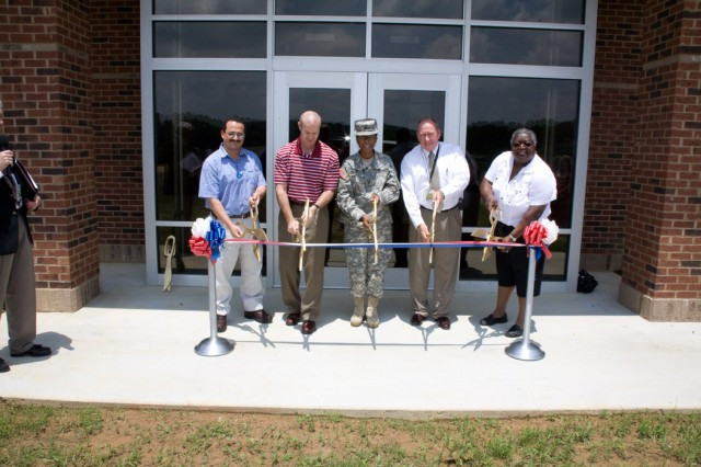 Alex Khamis, project engineer for the Anniston Army Depot's Directorate of Public Works; Phillip Trued, depot chief of staff; Col. S. B. Keller, depot commander; Jack Cline, deputy to the commander; and Thelma McCullough, retired former manager for the recycling center, cut the ribbon for the recycling program offices.