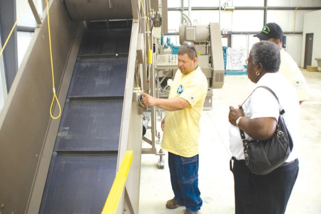 David Haynes starts the new shredder for Anniston Army Depot's recycling program as Earl Montgomery, leader of the Green Team, and Thelma McCullough, retired recycling manager, look on.