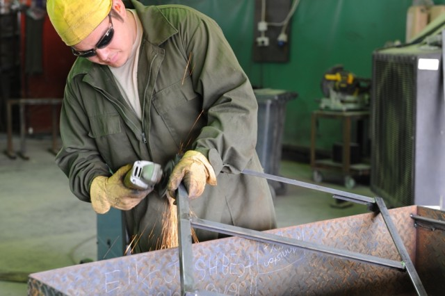 Anniston Army Depot welder Eli Careaga uses a grinder to polish a metal rack at the TACOM Life Cycle Management Command Forward Repair Activity in Kuwait.