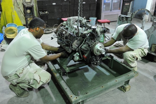 Anniston Army Depot heavy mobile equipment mechanics Antonio Allen, left, and Mark Thomas prepare a 6.5 engine at the TACOM Life Cycle Management Command Forward Repair Activity in Kuwait.