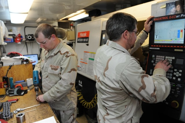 Working in the Mobile Parts Hospital at the TACOM Life Cycle Management Command Forward Repair Activity in Kuwait, Anniston Army Depot machinists James Francis, left, and Richard Payne create items to supplement the Army's system.