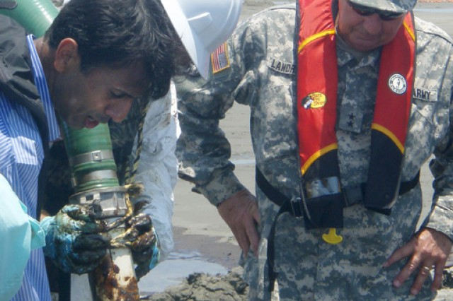 The governor of the state of Louisiana, Bobby Jindal, and Maj. Gen. Bennett C. Landreneau, adjutant general of the Louisiana National Guard, observe firsthand oil suction operations on East Grand Terre Island, June 9.