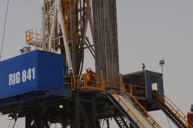Workers in hard hats check the workings of Weatherford rig site 841, which is now being prepared to begin pumping at Rumaila Oil Field in Basra Province. Rumaila is the largest oil field in Iraq with reserves of 17 billion barrels.