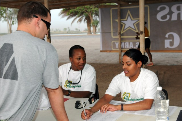 BAGHDAD - Sgt. Asha Salzer, patient administration noncommissioned officer in charge with the division surgeon's office, 1st Armored Division, helps a Soldier register for the Army birthday run June 14 at Camp Liberty. The 7-kilometer run started off the celebration of 235 years of Army strength. (U.S. Army photo by Spc. Daniel Schneider, 366th MPAD, USD-C)