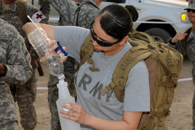BAGHDAD - Medic Spc. Denise Ismerio, assigned to Company B, Division Special Troops Battalion, 1st Armored Division, fills a spray bottle with water prior to a 7-kilometer Army birthday run June 14 at Camp Liberty. The spray bottles were used to spray down servicemembers and civilians after they passed to finish line to cool them down following the celebration.  (U.S. Army photo by Spc. Daniel Schneider, 366th MPAD, USD-C)