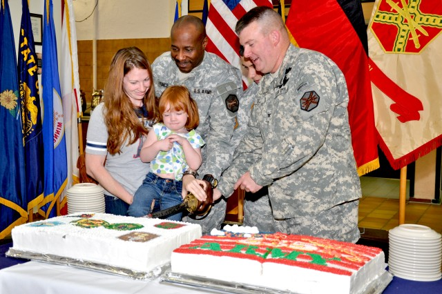 """Audrey Scarborough and her daughter Madilyn join Command Sgt. Maj. Hector Prince (from left), Pvt. 1 Juan Deluna and Col. Jeffrey Dill in cutting a cake at the Wiesbaden Dining Facility June 14 in honor of the Army's 235th Birthday. """"The history of the U.S. Army stretches back to June 1775; our nation recognized the need for a fighting force even before the signing of the Declaration of Independence,"""" said Dill, U.S. Army Garrison Wiesbaden's commander. """"Our Soldiers have proven their mettle time and time again -- 235 years of success in defense of our nation."""""""