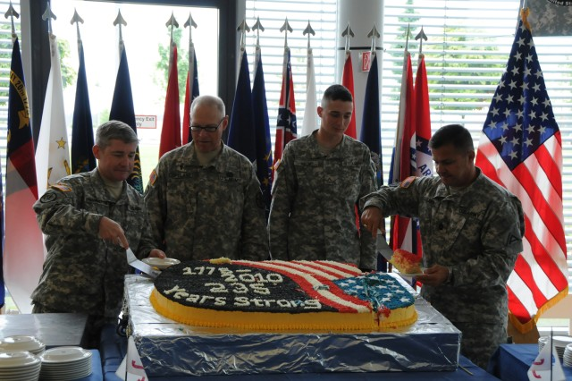 Col. Michael Higginbottom, chief of staff, Joint Multinational Training Command (left) and JMTC's Command Sgt. Maj. Darieus  Zagara serve cake to the oldest and youngest Soldiers, Chaplain (Maj.) Stan Copeland, 63, U.S. Army Garrison Grafenwoehr Family Life Chaplain and Pvt. Nathaniel Krom, 18, from Bravo Company, 3rd Battalion, 66th Armor Regiment, respectively, during the Army birthday celebration at USAG Grafenwoehr's Dining Facility, June 14. More than 400 Soldiers, civilians and family members attended the event.