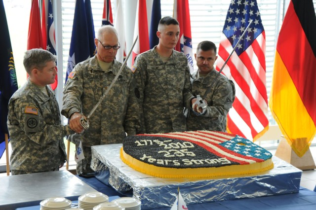 (From left to right) Col. Michael Higginbottom, chief of staff, Joint Multinational Training Command; Chaplain (Maj.) Stan Copeland, U.S. Army Garrison Grafenwoehr Family Life Chaplain; Pvt. Nathaniel Krom, Bravo Company, 3rd Battalion, 66th Armor Regiment; and JMTC's Command Sgt. Maj. Darieus  Zagara prepare to cut the cake during a celebration of the Army's 235th birthday at USAG Grafenwoehr's Dining Facility, June 14. More than 400 Soldiers, civilians and family members attended the event. Copeland, 63, and Krom, 18, were the oldest and youngest Soldiers, at U.S. Army Garrison Grafenwoehr. Copeland entered the Army 23 years before Krom was born.