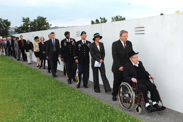 "Benjamin Gelhorn, the last living survivor of the World War II-era Concentration Camp Echterdingen, leads a group past the ""Ways to Remember"" memorial wall June 8 with his escort, followed by Filderstadt's Lord Mayor Gabriele Doenig-Poppensieker, USAG Stuttgart Commander Col. Richard M. Pastore, Command Sgt. Maj.  Anthony M. Bryant and others after the dedication ceremony of the Jewish memorial, which is located next to Stuttgart Army Airfield in Echterdingen. Some 119 Jewish detainees in the camp died during the winter of 1944/45. The memorial walls contain a sound system articulating the names of  the 600 Jewish detainees of the concentration camp."