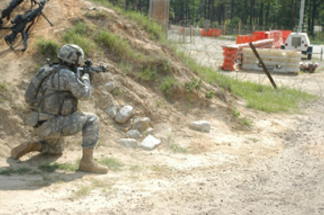 Sgt. Tighe Jenkins (right, behind barricade), 1st Battalion (Airborne), 509th Infantry Regiment attacks an entry control point at a rotational training unit forward operating base during an exercise at the Joint Readiness Training Center May 21. 1-509th serves as the opposing force during JRTC rotations.
