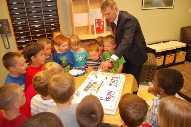 Joel Himsl, Garrison Manager, U.S. Army Garrison-Rock Island Arsenal, cuts the Garrison's cake recognizing and celebrating the Army's 235th Birthday with a room filled with children at the Arsenal's Child Development Center on June 14.