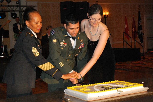 Sgt. Maj. Gloria Tyrell, Human Resources Command St. Louis, Spec. Michael Calvillo (the oldest and youngest Soldiers present, respectively,) and Melissa Banian, representing the spouses of deployed Soldiers, cut the 2010 Army Birthday Cake with a saber during the Mid-America Army Birthday Ball June 12 in St. Louis.