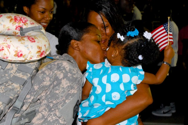 A Soldier sneaks a kiss in from her loved one after spending nine months away from home. The 15th Sustainment Brigade redeployed more than 200 Soldiers from Iraq May 30 at Fort Hood, Texas. (U.S. Army photo by Sgt. 1st Class Erick Ritterby)