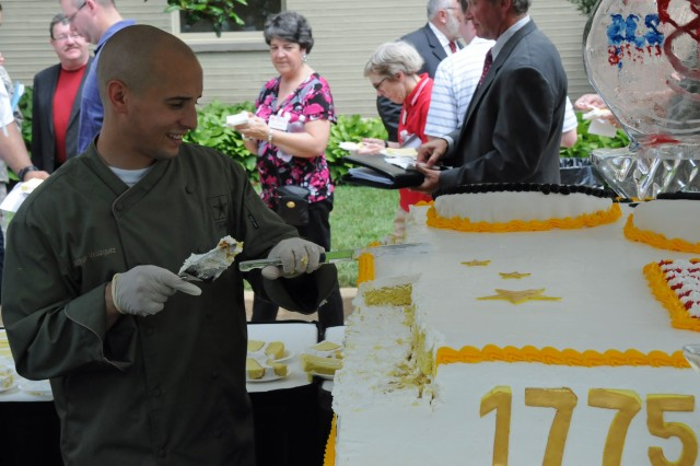 Sgt. Jonathan Velazquez cuts a piece of the giant Army birthday cake for guests at the Pentagon.