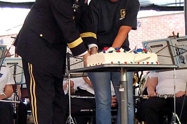 CHARLOTTESVILLE, VA -- Brig. Gen. John W. Miller II, commander/commandant, U.S. Army Judge Advocate General's Legal Center and School; and Future Soldier Hannah Wright, 18, slice into the Army's 235th birthday cake during a community celebration at the Charlottesville pavilion June 14. Wright, who only weeks ago was finishing up her senior year at Open Door Christian School, will be leaving at the end of the month for basic training at Fort Jackson, S.C. Joining the Army was a life-long dream, said Wright, who's uncle served in the Army. She's currently working with her recruiter to prepare for her military training. Wright along with more than 15 Future Soldiers from the Lynchburg Recruiting Company participated in a swear-in ceremony during the Army's birthday celebration.