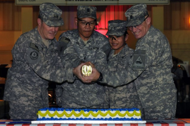 BAGHDAD - During the Army's 235th birthday celebration at Camp Liberty, (from left to right) Maj. Gen. Terry Wolff, commanding general of United States Division - Center, Sgt. Maj. Danilo Diaz, Pvt. Sepe Salik and Command Sgt. Maj. Sal Katz, the senior enlisted noncommissioned officer of Division Special Troops Battalion, prepare to cut the Army's birthday cake. Traditionally, the cake is cut by the oldest member of the division, Diaz, logistics and supply sergeant major, and the youngest, Salik, a food service specialist of Company B, DSTB, 1st Armored Division.  (U.S. Army photo by Spc. Daniel Schneider, 366th MPAD, USD-C)