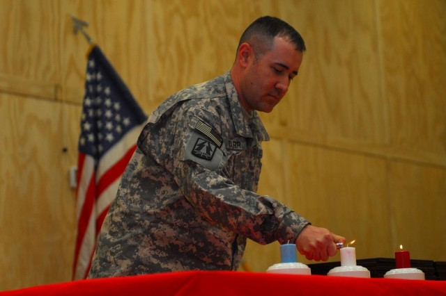 Sgt.1st Class Jason Starr, communications chief for 1st Bn., 377th FA Regt. and native of Denton, Texas, lights the white candle representing the present and purity during the noncommissioned officer induction ceremony at the Contingency Operating Base Basra chapel May 31, 2010. The ceremony commemorates the rite of passage of recently promoted Soldiers and honors the memory of prior noncommissioned officers