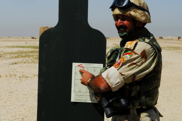 """A 14th Iraqi Army Division, 52nd Brigade officer is pleased after assessing his target on a range near Joint Security Station Sa'ad June 5, 2010. When zeroing, shots close together indicate a good """"shot group,"""" and further adjustments to the weapon will move toward the silhouette."""