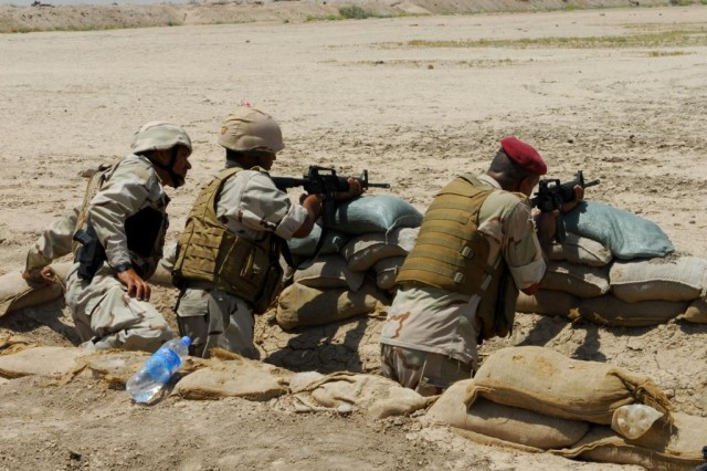 Lt. Qassm, an Iraqi officer with the 52nd Brigade, 14th Division,, coaches other 52nd Bde. soldiers as they fire at paper targets at a range near Joint Security Station Sa'ad June 5, 2010. The first firing order was comprised of 52nd Bde. officers who were coached by U.S. forces. The officers then coached the next firers.