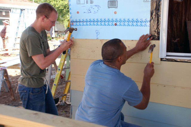 Two members of the 717th Military Intelligence Battalion attach siding to a house in a volunteer project for Habitat for Humanity. (Photo by Gregory Ripps)