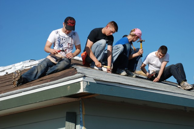 Off-duty Soldiers from the 717th Military Intelligence Battalion position and nail roofing into place on a house for Habitat for Humanity. (Photo by Gregory Ripps)