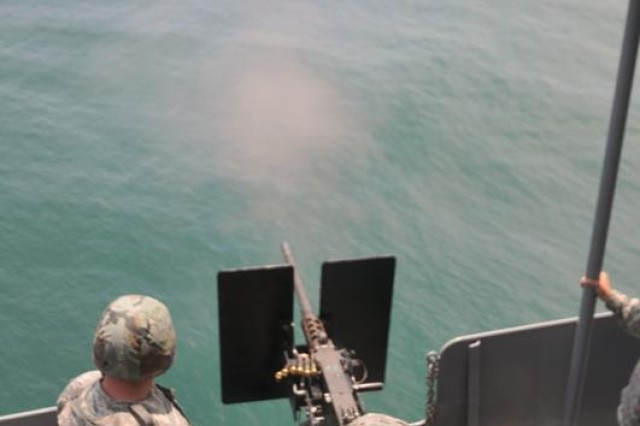 Private 1st Class Jacqueline Washington, a watercraft operator assigned to the 335th Transportation Detachment, 24th Transportation Battalion, aims for the water buoy while firing the M2 .50 caliber machine gun Saturday afternoon. (U.S. Army photo by Sgt. 1st Class Kelly Jo Bridgwater)