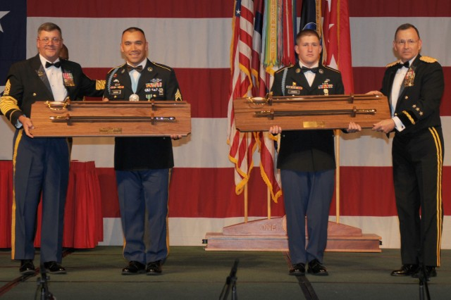 HONOLULU, Hawaii-- Staff Sgt. Eddie Barba an Infantry squad leader assigned to Company A, 1st Battalion, 5th Infantry Regiment, United States Army Alaska, and Spc. Andy James an infantryman assigned to Company B, 2nd Battalion, 27th Infantry Regiment, 3rd Brigade Combat Team, 25th Infantry Division receive noncommissioned officer sword plaques after being announced winners of the 2010 U.S. Army-Pacific Warrior Challenge Competition during the 235th Army Birthday Commemoration, at the Hilton Hawaiian Village, here, June 12.