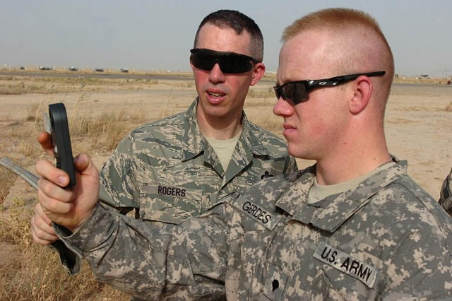 Air Force Master Sergeant Paul Rogers, weather forecaster and staff weather team noncommissioned officer incharge, 22nd Expeditionary Weather Squadron, supporting TF Wings, teaches a Soldier how to perform weather checks measuring winds, temperature, dew point and pressure with a handheld Kestrel at Contingency Operating Base Speicher, near Tikrit, Iraq, June 5. (Photo by: Staff Sgt. Mike Alberts, 25th Combat Aviation Brigade Public Affairs)
