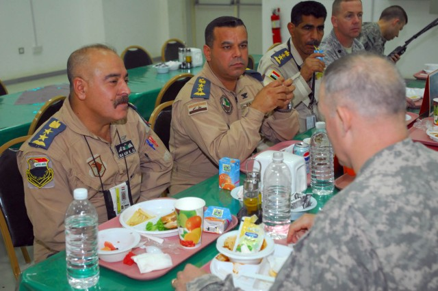 Col. Saadi, Iraqi chief of staff of Ali Air Base, and Col. Nazih al-Fahaed, commander of the 70th Squadron, Iraqi Air Force, have lunch with Brig. Gen. Ricky Gibbs, the Deputy Commanding General for Maneuver, 1st Infantry Division, June 2 on Contingency Operating Base Adder, Iraq, as part of the ongoing process to transfer 70th Sqdn. to Ali Air Base from Basra in the coming months.