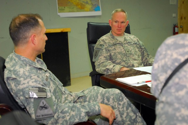 Col. Robert Doerer, commander of the 12th Combat Aviation Brigade, Task Force 12, talks with Brig. Gen. Ricky Gibbs, the Deputy Commanding General for Maneuver, 1st Infantry Division, June 2 at Contingency Operating Base Adder, Iraq, about the ongoing plans to transfer the 70th Sqdn. from Basra to Ali Air Base and the continuing partnership training with Iraqi Security Forces.