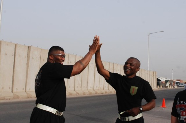 Master Sgt. Shawn Harris(left), 1st Infantry Division electronic warfare noncommissioned officer, and Chap. (Capt.) Johnvianney Ijeoma, the 1st Inf. Div. Headquarters and Headquarters Battalion chaplain, high five after completing the Army Birthday 12K Run, 5K Walk at Contingency Operating Base Basra June 12. The run/walk was just one of dozens of events held across Iraq, Kuwait and the U.S. to celebrate the Big Red One and Army birthdays.