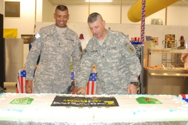 Maj. Gen. Vincent Brooks and Command Sgt. Maj. Jim Champagne, the commanding general and senior noncommissioned officer of the 1st Infantry Division, cut the Army Birthday cake at Contingency Operating Base Basra's Fighting First Dining Facility June 14.  1st Infantry Division Soldiers celebrated Big Red One and Army birthdays in Iraq at Basra, Taji, and Tikrit; in Kuwait; and in the U.S. at Forts Riley, Knox, Leonard Wood and Sill.