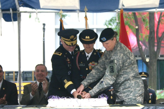 Maj. Gen. Yves J. Fontaine, commanding general of ASC,  Rock Island Arsenal, Ill., participates in the cake-cutting ceremony at Daley Plaza in Chicago June 14. Assisting Fontaine is an Army cadet (center) and an Army noncommissioned officer.