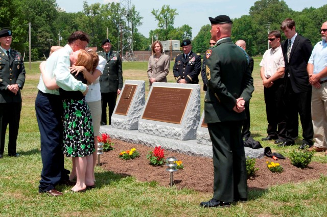In the long moment of silence following the unveiling of the monument, Douglas Mauzy and widows Christina Gray, front, and Trudy Henry embrace. Mauzy is the lone survivor of the May 21, 2009 accident, which took the lives of his coworkers Mark A. Henry and Joseph E. Gray. (U.S. Army photo courtesy of Aberdeen Test Center)