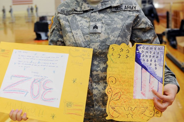 "PRESIDIO OF MONTEREY, Calif. - Sgt. Olga Silberman, Co. F, 229th Military Intelligence Battalion, displays two of her favorite pieces from a package of artwork and letters sent from Miami Central Senior High School students for Memorial Day. ""I appreciate all the support through all the good and bad times,"" said Silberman. ""I am proud to serve the country on behalf of all people."""