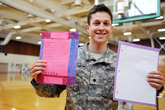 "PRESIDIO OF MONTEREY, Calif. - Spc. David Marcus, Co. A, 229th Military Intelligence Battalion, displays two letters that caught his eye from Miami high-school students. Marcus admitted that he did not fully understand the students' letters completely, but enjoyed reading what he could. ""These students help to enrich the American spirit,"" Marcus said. ""I am very thankful that they are a part of us."""