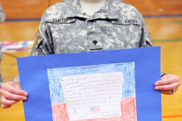 "PRESIDIO OF MONTEREY, Calif. - Spc. Micky Curtis, Co. A, 229th Military Intelligence Battalion, displays one of her favorite letters from Miami high-school students. ""Thank you for all the letters, especially the ones with return addresses,"" Curtis said. ""I wish I could write you all back, but we are learning (other) languages, too,"" she added, referring to the Miami students' English as a second language curriculum. Curtis said she intends to write one student back as a ""thank you."""