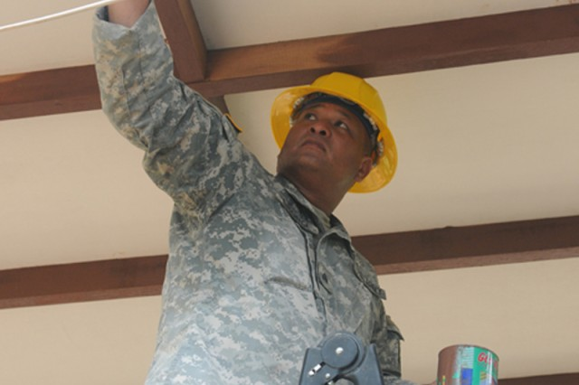 Sgt. James Chong paints the eaves during the construction of a baby-care clinic. The clinic is one project involved in Operation Garuda Shield 2010, a seven-nation humanitarian and training exercise here set to complete June 21. Members of the 797th Engineering Company, 411th Engineering Battalion, 9th Mission Support Command are also constructing a community civic center, bathhouse and a water-retaining system.