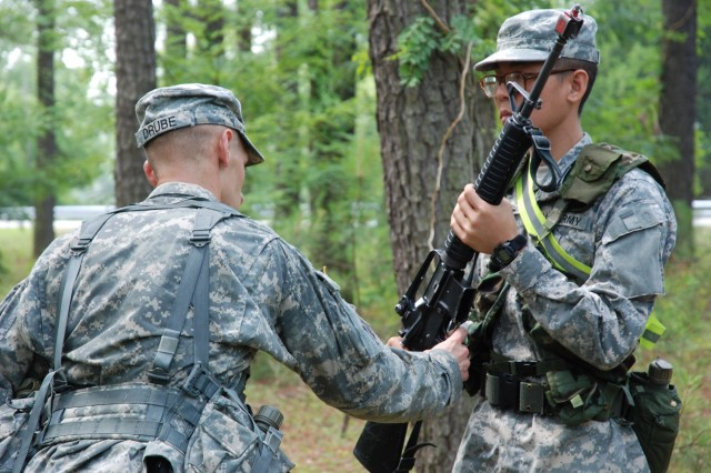 Staff Sgt. Kyle Drube (95th Reserve Division) reminds a Soldier to keep the safety on while inspecting arms during the 2010 Drill Sergeant of the Year competition at Fort Eustis, Va. The winner of the Army-level competition will be named on June 18 at Fort Monroe, Va.
