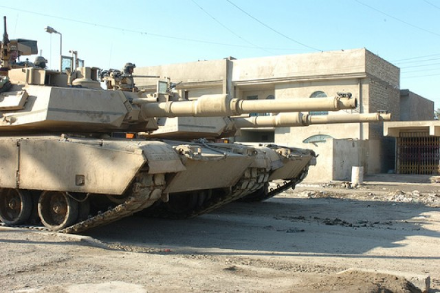 Two massive M-1 Abrams Tanks from 1st Battalion, 5th Cavalry Regiment, provide over watch for Soldiers from Company B, 2nd Battalion, 12th Infantry Regiment, attached to the 1st Cavalry Division's 2nd Brigade Combat Team, while on patrol in the Al Doura district of Baghdad.
