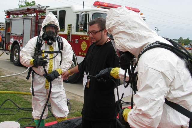 Detroit Arsenal firefighters Stephen Varnado (left) and Dan Lehman spray water on David Terry, an exercise volunteer, during the personnel decontamination portion of the Vigilant Guard exercise.