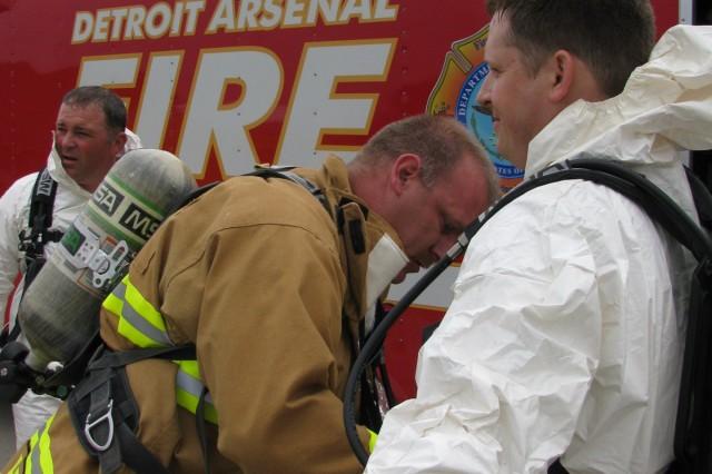 Detroit Arsenal firefighter Brad Breiler seals the bio hazard suit of Stephen Varnado during the personnel decontamination portion of the Vigilant Guard exercise.