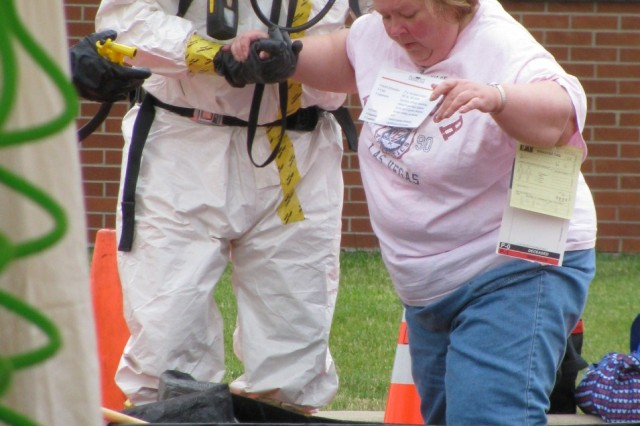 Detroit Arsenal firefighter Dan Lehman helps Kathy Linville, an exercise volunteer, into the first station during the personnel decontamination portion of the Vigilant Guard exercise.
