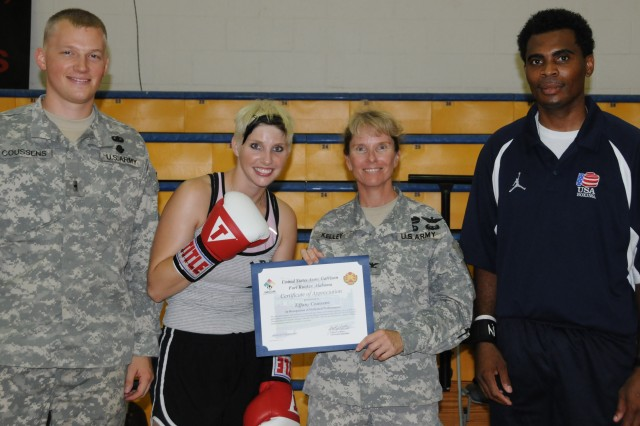 From left, flight school student Chris Coussens, his wife Tiffany, Garrison Commander Col. Yvette Kelley and Coach Kevin Green celebrate Tiffany's certificate of appreciation from Kelley June 4 at the Fort Rucker Physical Fitness Facility. Coussens trained and qualified for the Female Golden Gloves National Tournament and the U.S. National Championships through the support of her husband and coach.