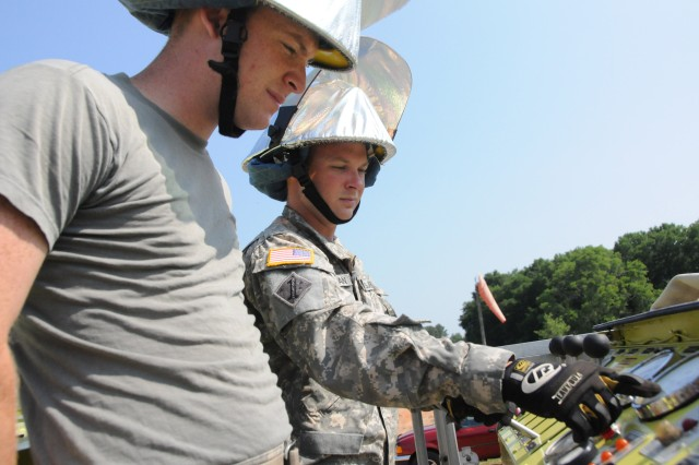 Spc. Josh Seligman, right, instructs Spc. Brenden Besaw on how to use a throttling pump and check pressure gauges on a fire truck at Fort Rucker's Hanchey Army Heliport June 14.